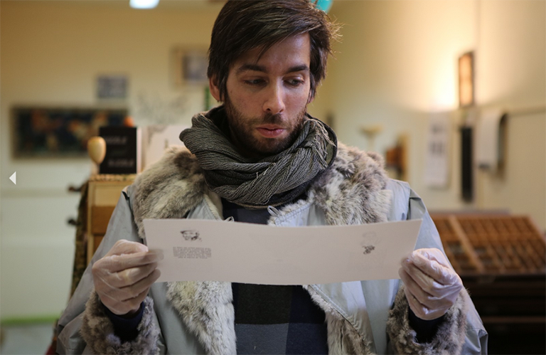 Tucker Kapp (C'10) poses in his workshop with a white scroll of paper