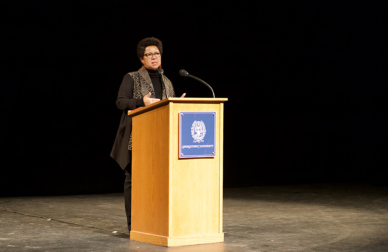 A woman speaks at a podium with Georgetown's seal on the front.