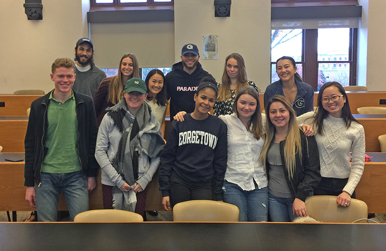 A class of 11 students poses in their classroom with their professor.