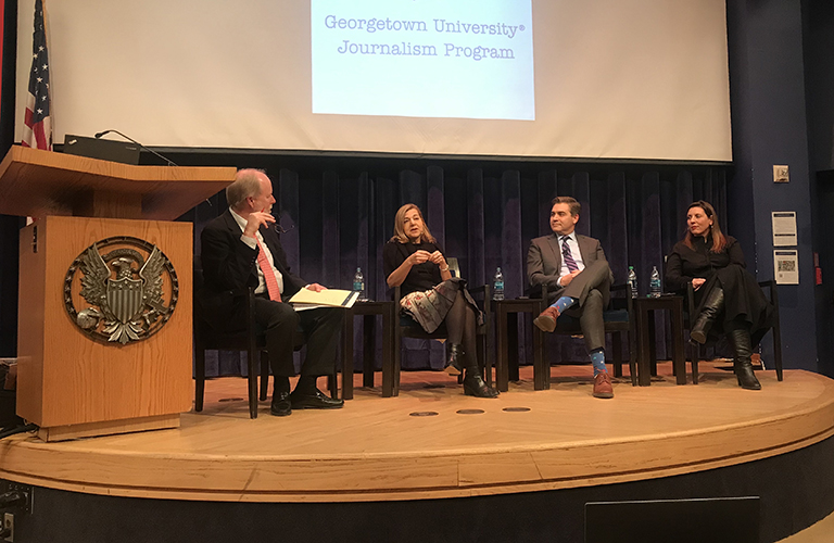 Three panelists from national news organizations discuss journalism on a stage with program director Doyle McManus