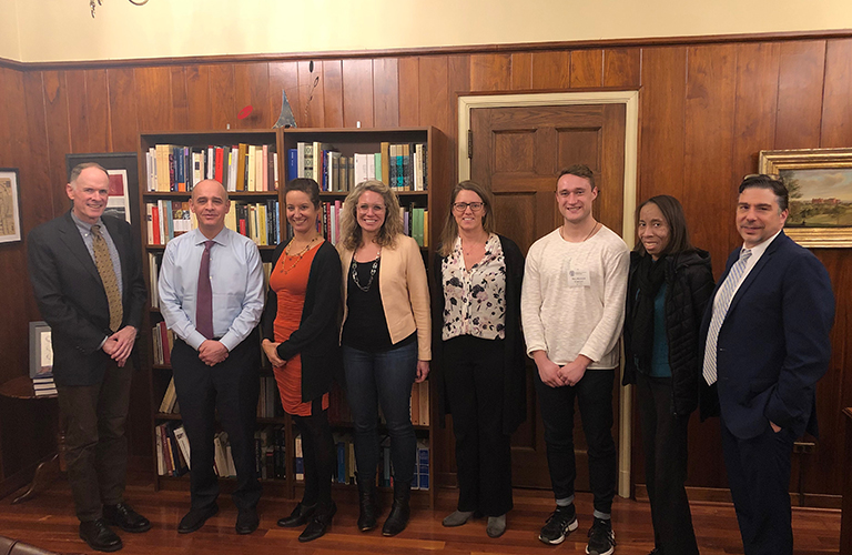 Members of the Social Responsibility Network board pose with Dean Celenza in a wood-paneled office in front of a bookcase
