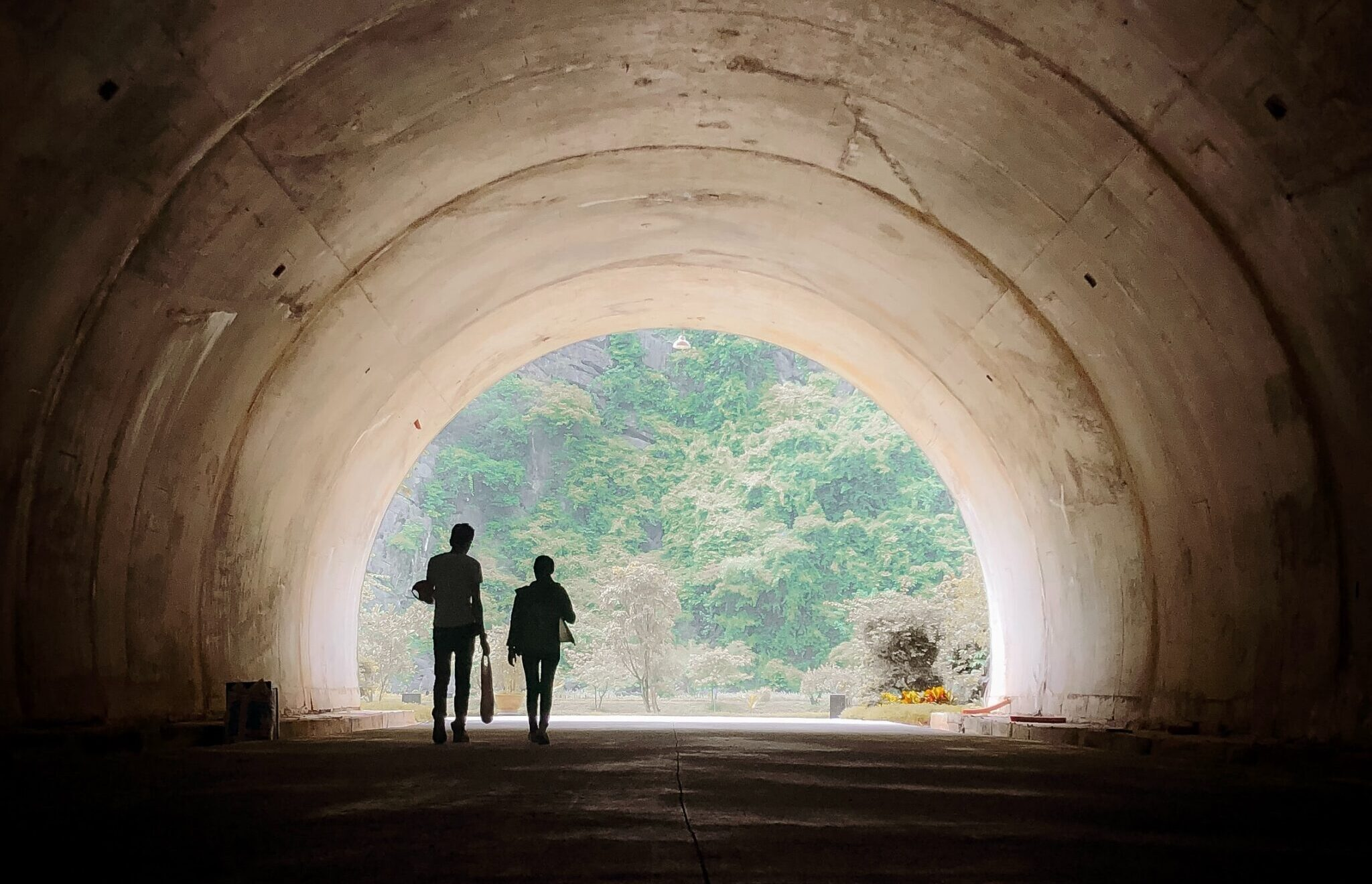image of two people walking through a tunnel