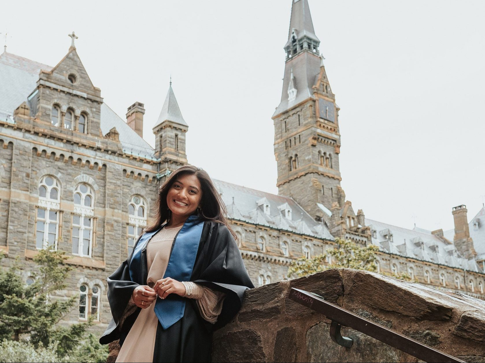 photo of jaipaul in graduation regallia with healy hall in background