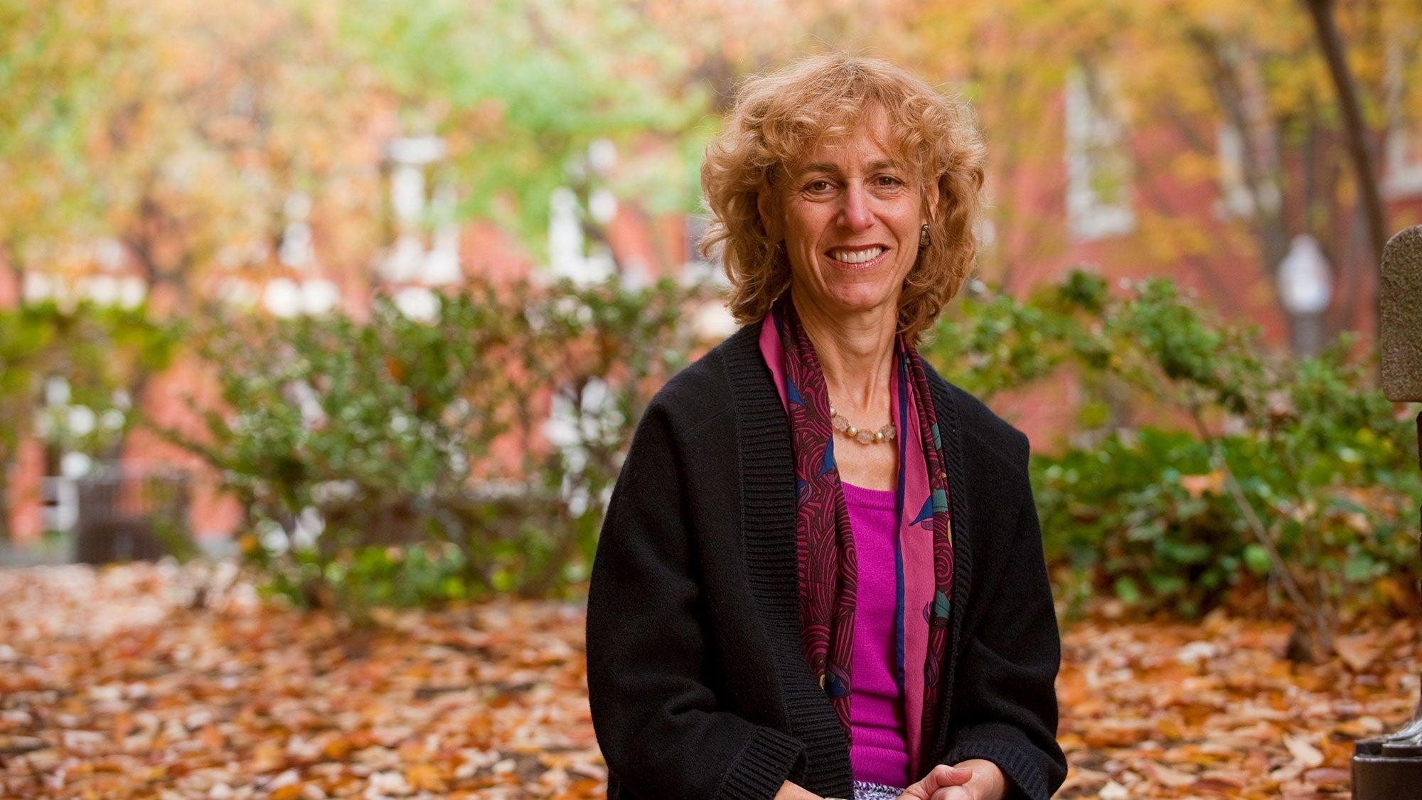 Headshot of Nancy Sherman sitting outside on bench in fall leaves