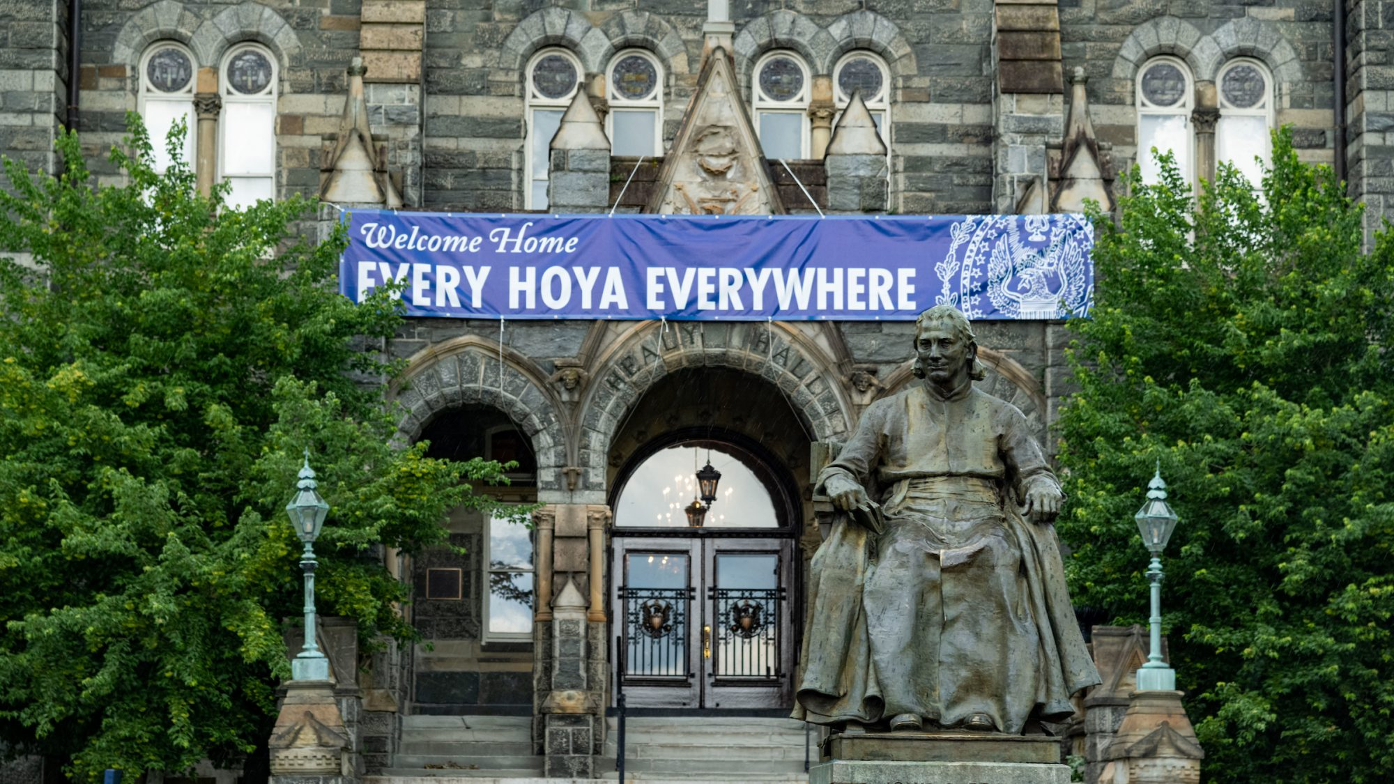photo of john carroll statue with flag behind that says every hoya everywhere