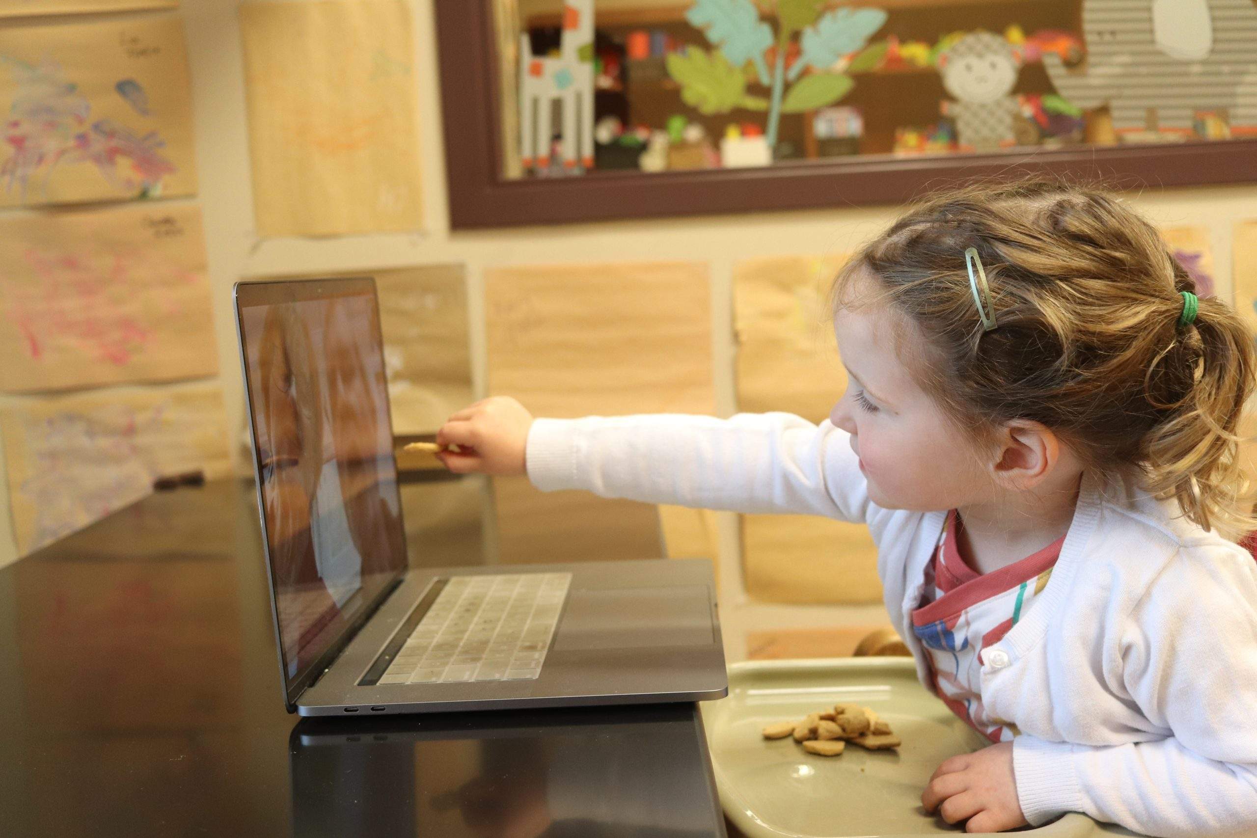 Photo of Child Reaching for computer screen where grandparents are calling in from videochat