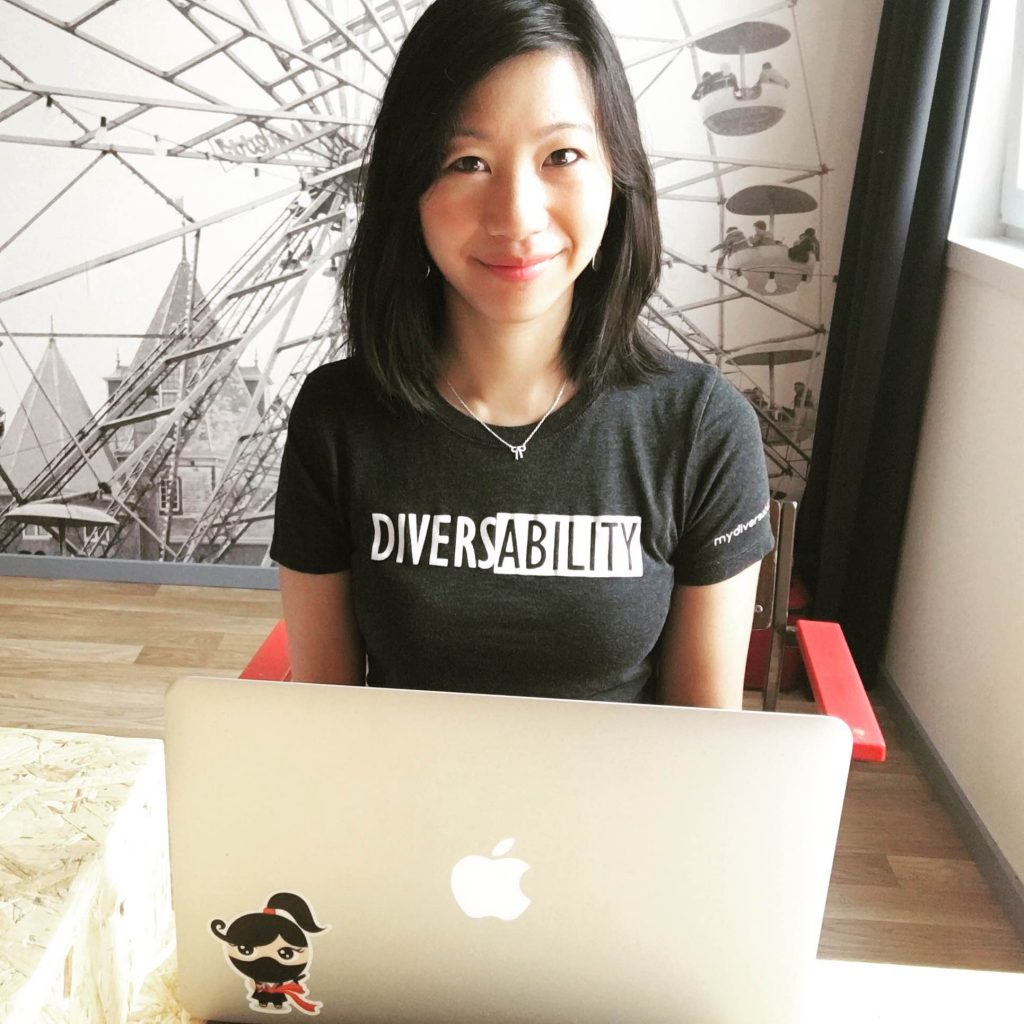 Tiffany Yu sitting in front of a computer where a diversability tshirt