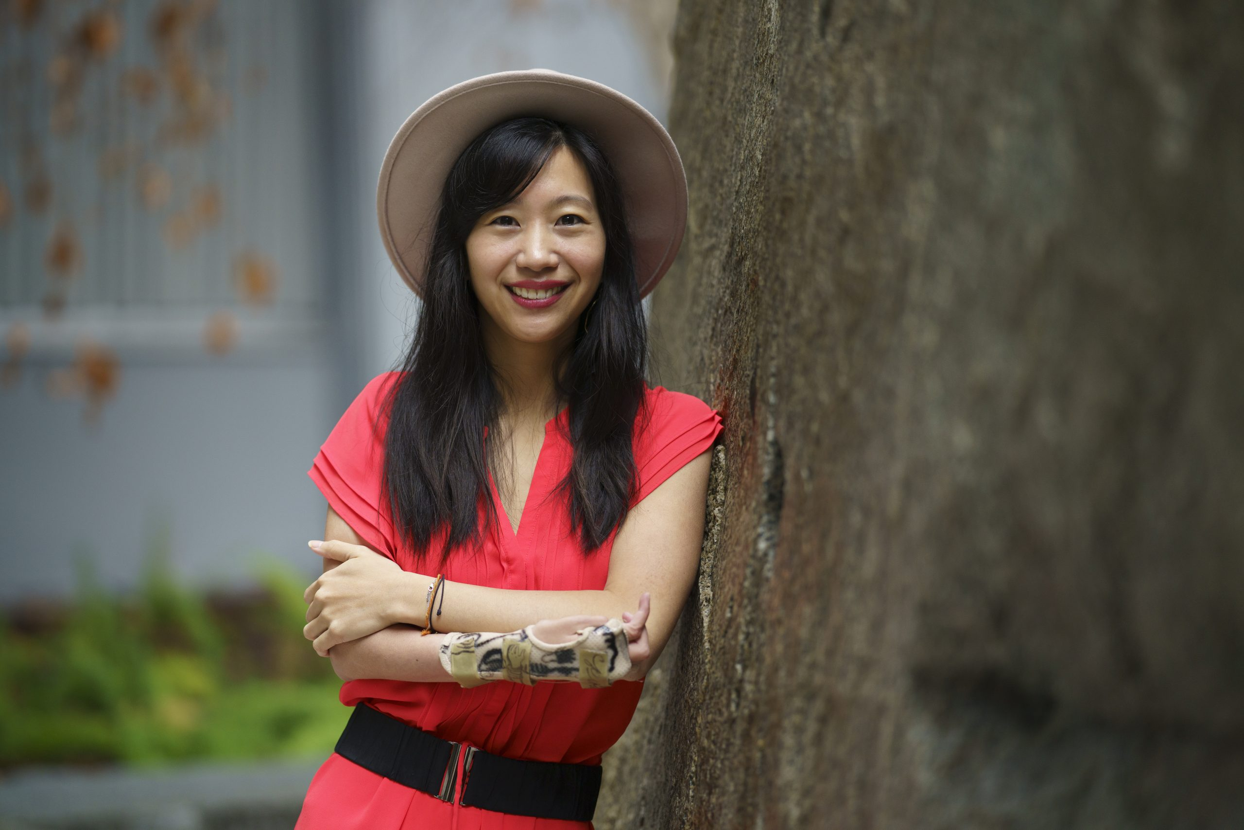 photo of Tiffany Yu in a red dress and hat leaning against a tree smiling