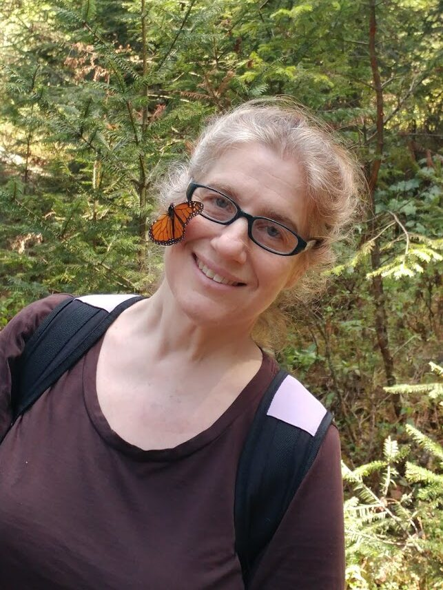 photo of Leslie Ries smiling in the forest with a monarch butterfly perched on her cheek.