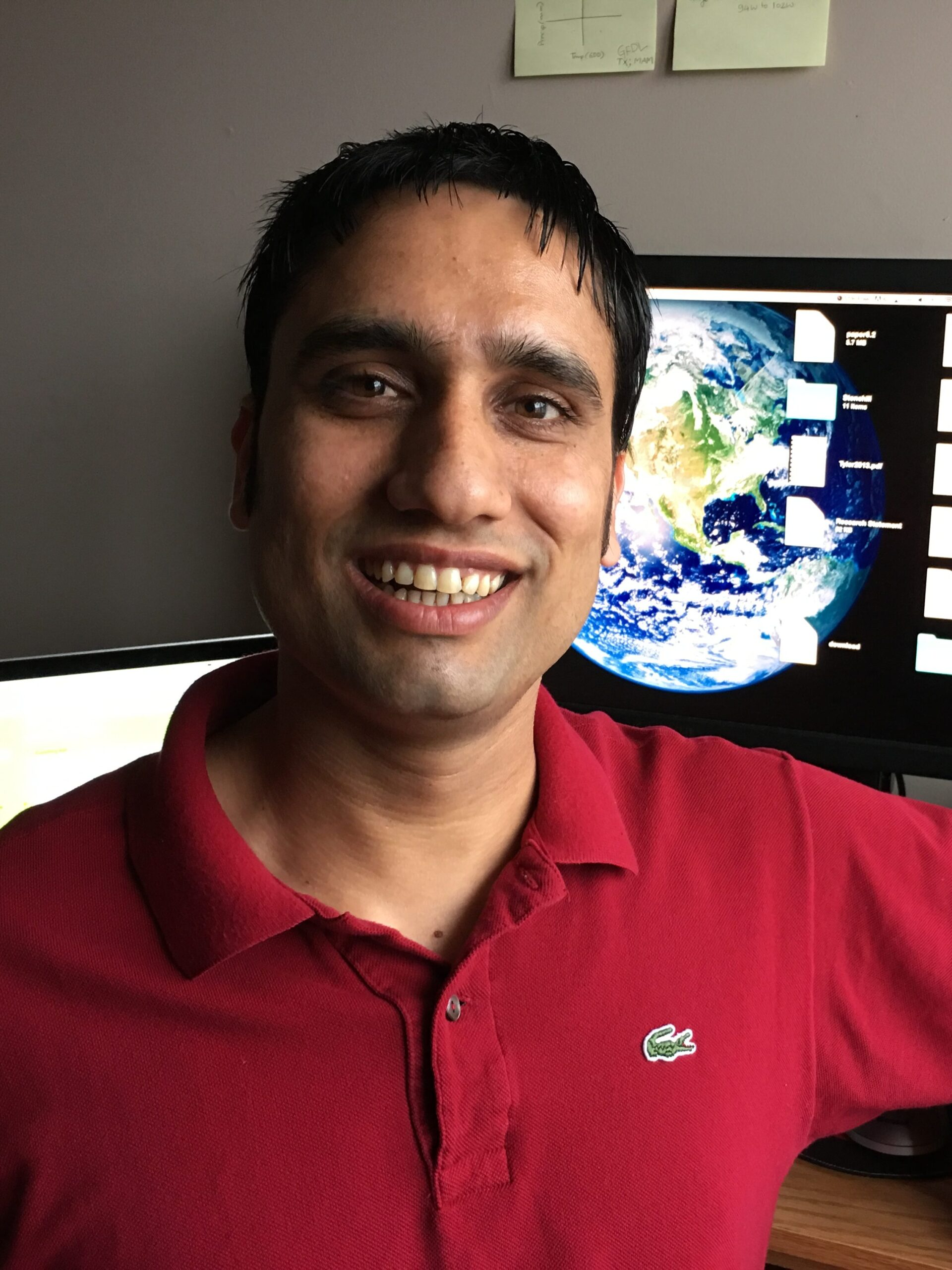photo of Naresh wearing a red shirt and smiling at the camera in front of a computer with a desktop image of the world
