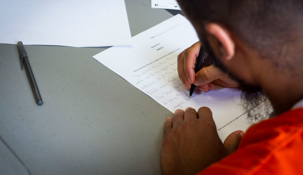 photo of an incarcerated individual writing on a piece of paper