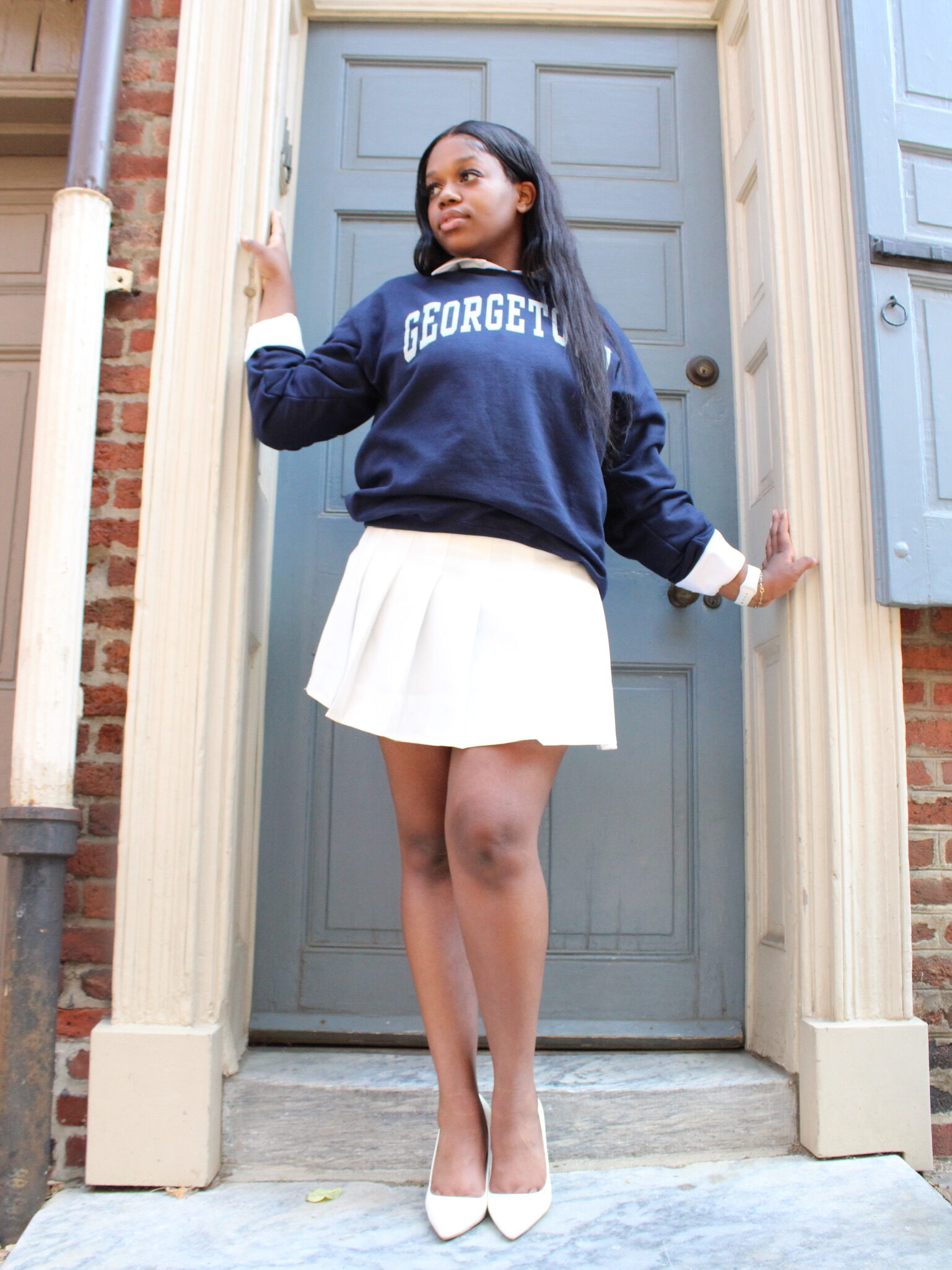 Rams-Lyne stands in front of a sage green door with her hands on the frame. She is looking off camera to the left. She is wearing white heels, a white tennis skirt and a navy Georgetown sweatshirt.