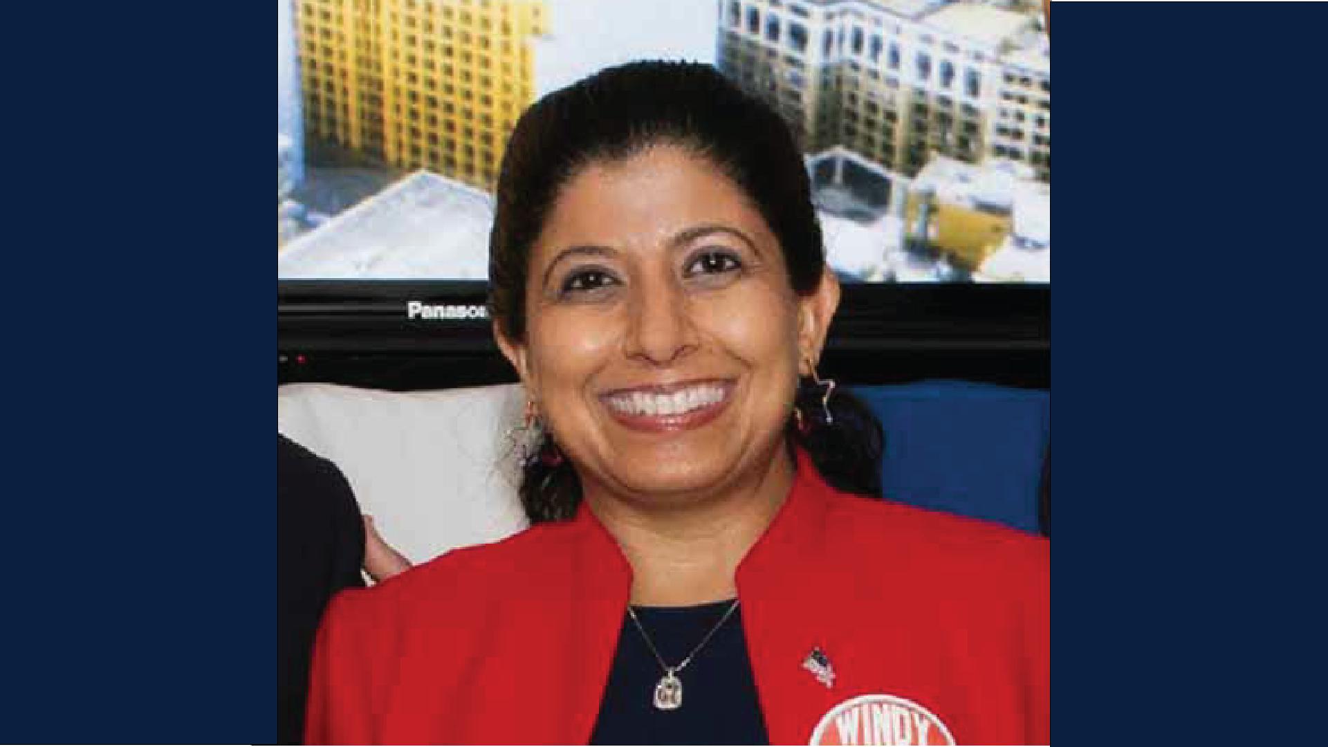 headshot of Nazima Rasick wearing a red blazer and smiling
