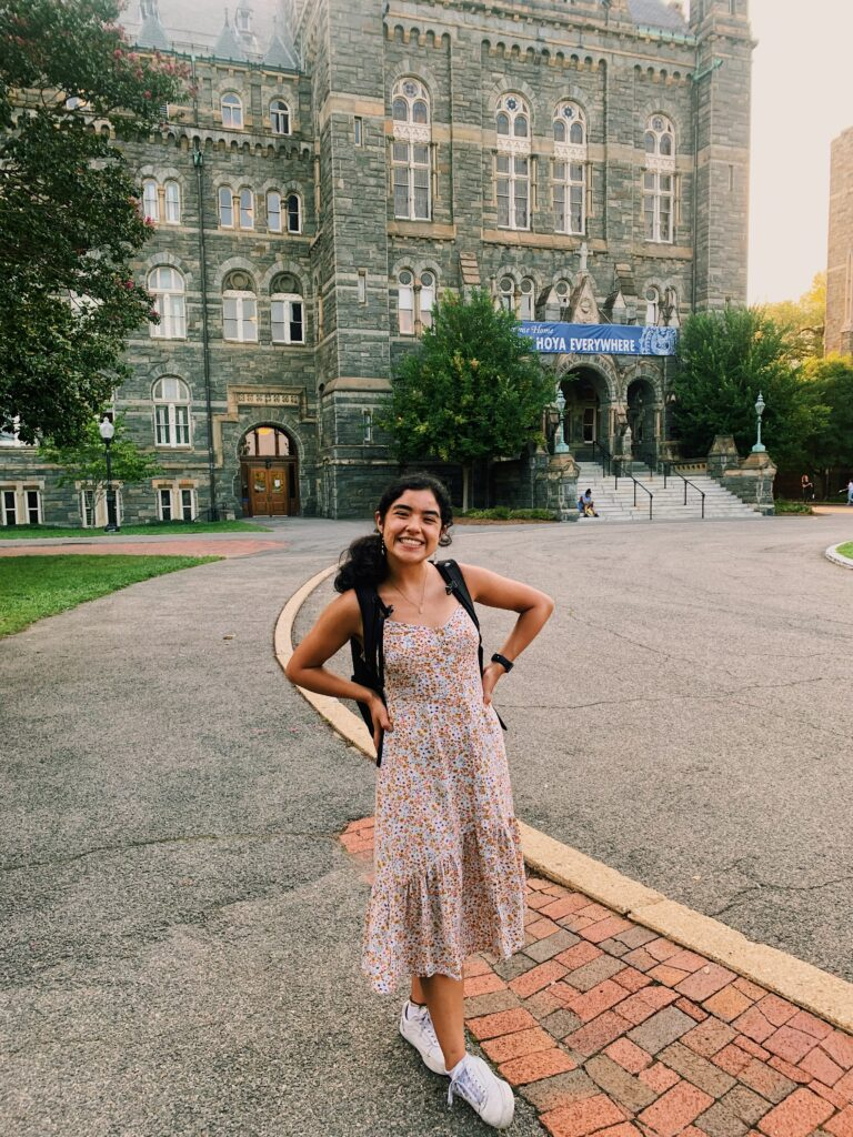 Dayree smiling as she stands with her hands on her hips in front of Healy Hall. She is wearing a flowing floral pattern dress