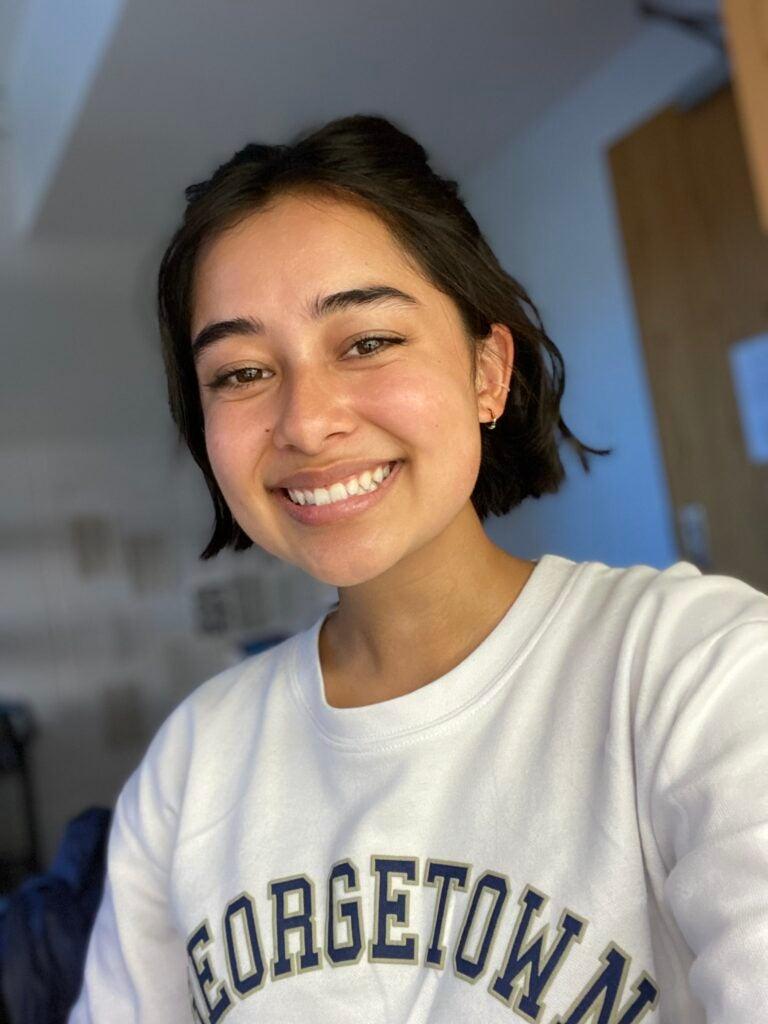 Logan smiling in a selfie wearing a white Georgetown sweatshirt