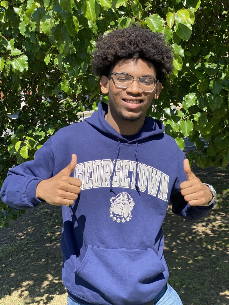 Jaden smiling and giving two thumbs up to the camera. He is wearing a navy blue Georgetown hoodie with a bulldog on it
