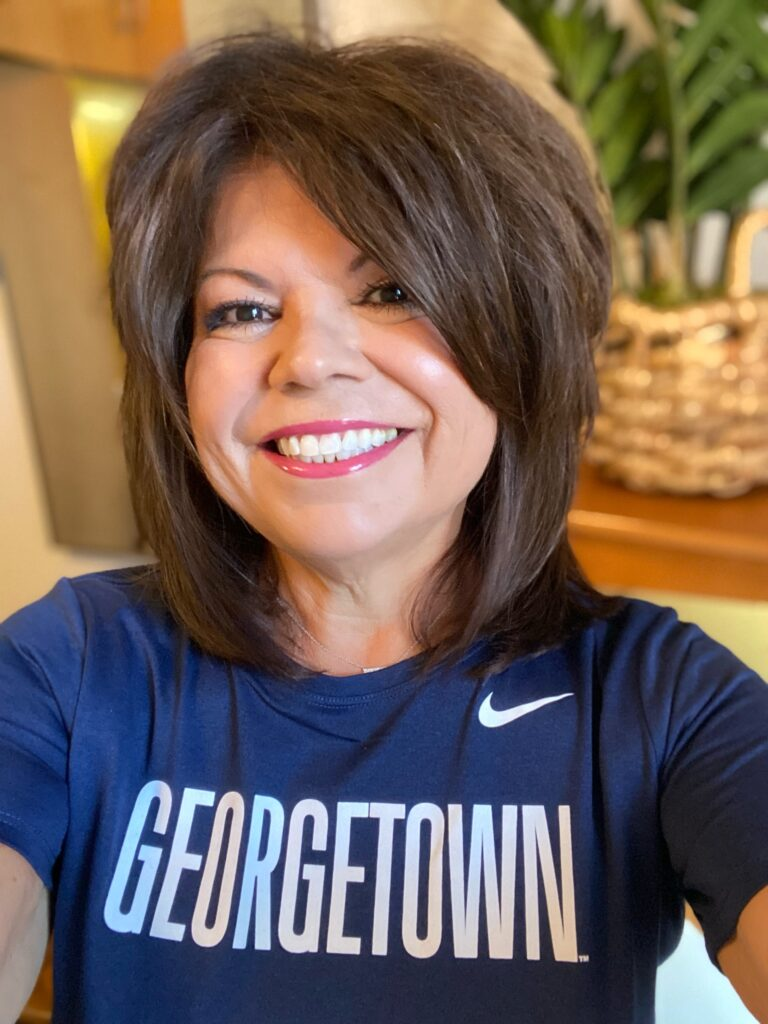 Laura smiles into the camera as she takes of selfie of her wearing a navy athletic shirt with a white nike logo on it.