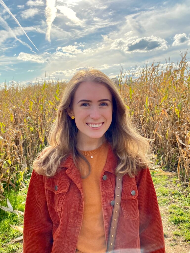 Maureen smiles into the camera as she stands in a field. She is wearing a brownish-red corduroy jacket over a burnt orange shirt.