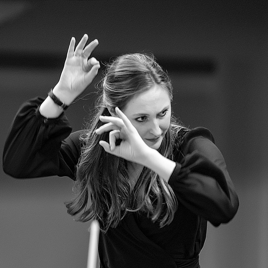 live action black and white shot of hannah conducting